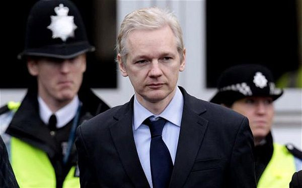 The founder of secret-spilling website WikiLeaks Julian Assange is flanked by police officers as he leaves the court after making an appearance at Belmarsh Magistrates' Court in London, Tuesday, Jan. 11, 2011.  Assange is in court Tuesday for a procedural hearing which lasted for only about 10 minutes, as part of his fight to avoid extradition to Sweden on allegations of sex crimes.  (AP Photo/Lefteris Pitarakis)